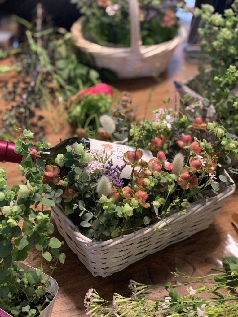 a bottle of wine in a basket flower arrangement